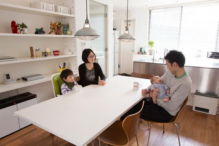 ダイニングテーブルでくつろぐ浦野家の一家4人。左が奥さんと長男の優作君。右が浦野さんと俊介君。テーブルのライトはジェイルペンダント。「工場っぽいのが面白い」と思い購入したものという。