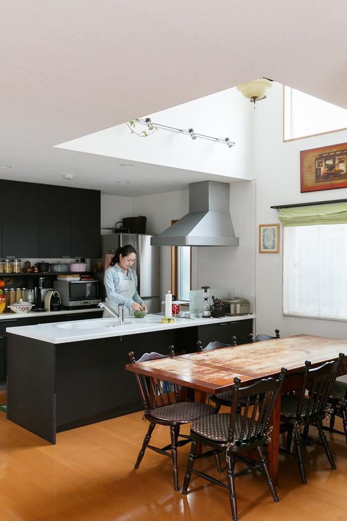 使い勝手よく作りあげたダイニングキッチン。天井が吹き抜けのため、開放感がある。キッチンの色味は他の家具にあわせてチョイス。北海道民芸の椅子は「北民色」と呼ばれる濃い色合いが美しい。