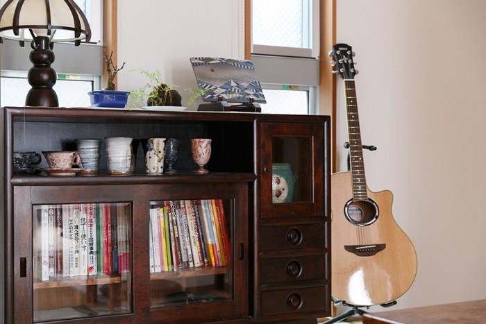 重厚なつくりの松本民芸の棚は本棚兼飾り棚に。料理やお酒の本が並ぶ。