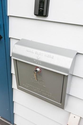 下見張りの白い外壁、ブルーの玄関ドア、シルバーのアメリカ製のポストが、平屋の家によく似合う。
