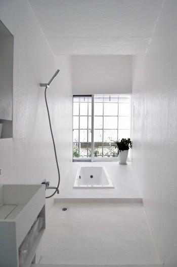 1階奥にあるバスルーム。細長い台形平面と床を掘ってつくったバスタブが印象的。