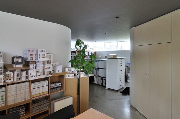 玄関入ってすぐの打ち合わせスペースから事務所内を見る。左右のアールの壁は、外形のアールの形がそのまま反映している。この半地下スペースは年間を通して過ごしやすいという。