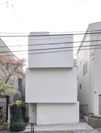 高い建物に挟まれた紀野邸。道路側にはまったく窓が開けられていない。左のアプローチ部分の塀際にはハーブが植えられている。