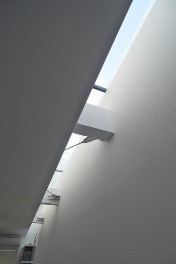 2階の細長い寝室には建物のサイドに設けられたトップライトから光が注ぎ込む。