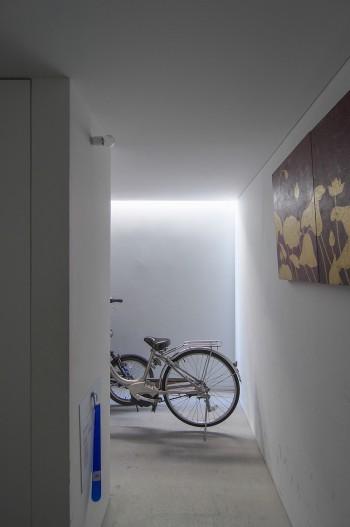 玄関を開けて正面の空間は奥に向かって自転車などを置くスペースになっている。昼間はトップライトの光のみで十分明るい。