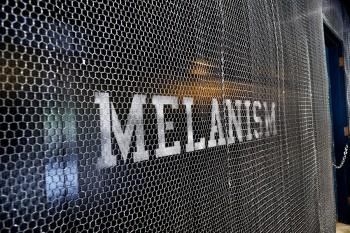 店内奥の壁面にテーマ「MELANISM」が掲げられている。