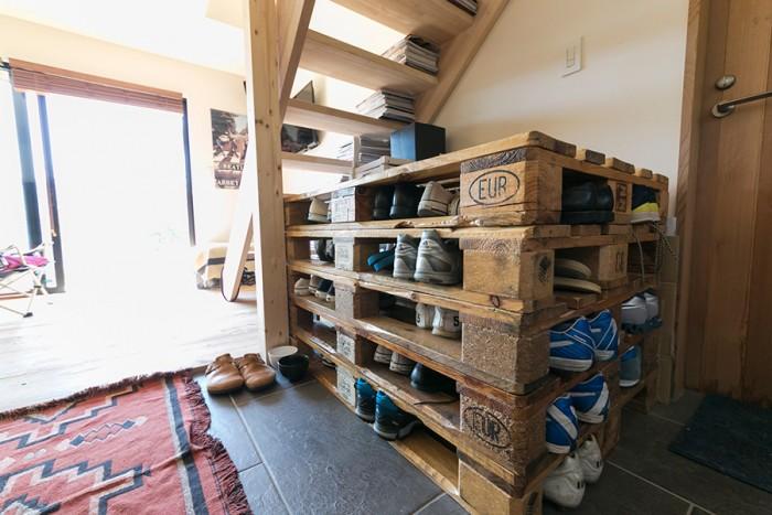玄関ドアを明けると広いタイル敷きの空間になっていて、そこもリビングの一部になっている。靴はパレットに収納。