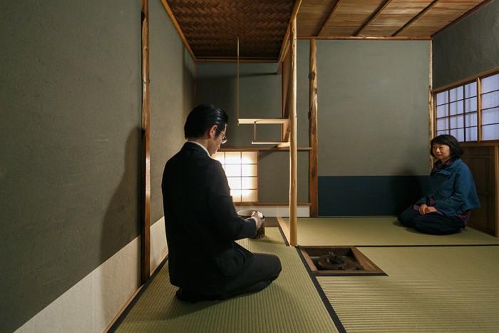 「小間」と呼ばれる茶室でお茶を点てる岸本さんと鯰組広報の堀田さん。萩の網代天井は、今ではなかなかつくれないものだそう。
