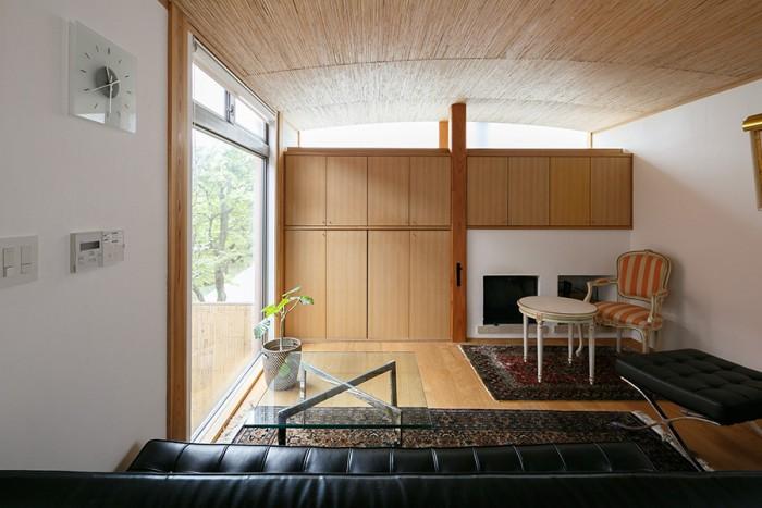 リビングの天井の材は葦。ゆるく湾曲させ、地下の竹天井と呼応させている。造りつけの収納棚を閉めればテレビなども隠れてすっきりした印象に。「オレンジのアンティーク椅子は妻の嫁入り道具です」。