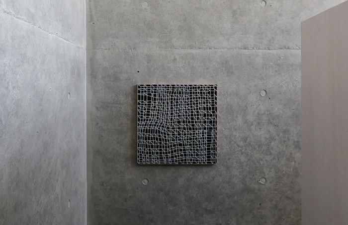 藤田さんからの建築家へのリクエストには「ギャラリーのようにアート作品が展示できる室内空間」もあった。地下へと降りる階段正面の壁には額田宣彦さんの作品がかけられている。