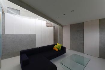地下のリビングスペース。壁面収納の裏に階段と玄関がある。