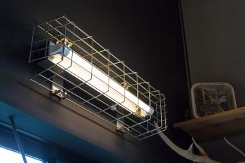 倉庫や工場などで使われるワイヤーのガードがついた照明器具。インダストリアルな雰囲気がクール。