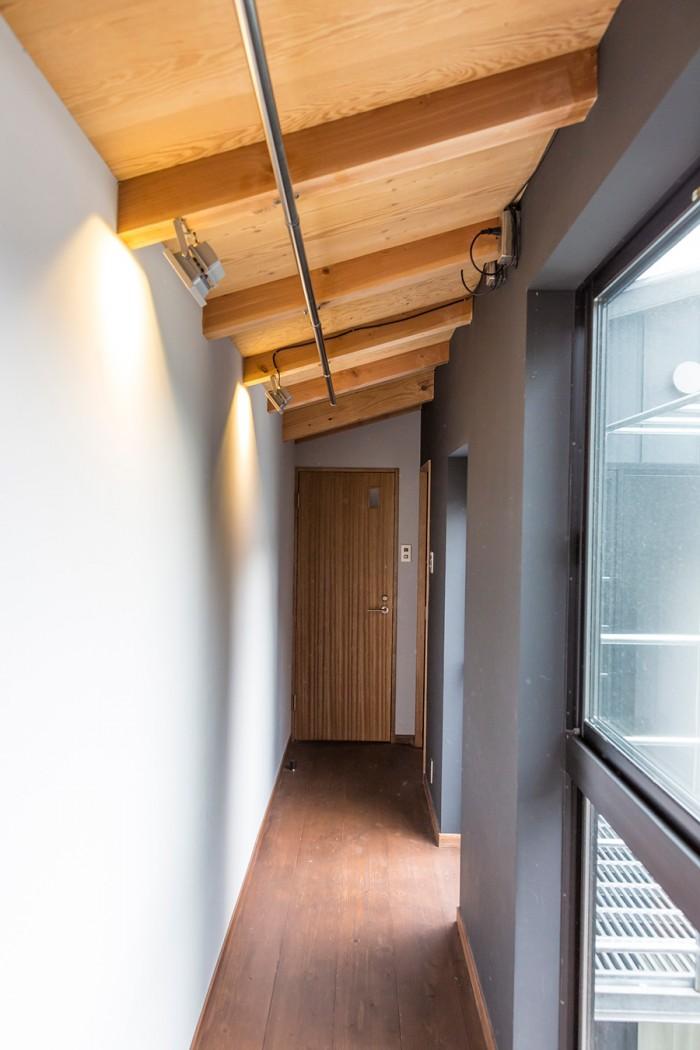 バスルームに向かう渡り廊下。天井のパイプは雨の日の洗濯物干しで活躍。スタジオライトのようなデザインの照明がカッコいい。