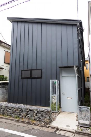 黒のガリバリウム鋼板の外観。郵便物の投函口のついたグレーの玄関ドアがキュート。