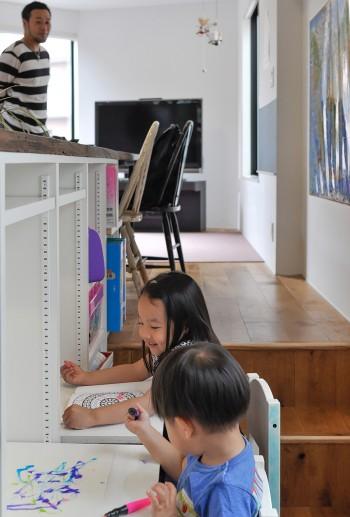 キッチン前の廊下スペースに神林さんがつくった子ども用の作業台でお絵描きをして遊ぶ姉弟。