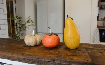 キッチン前の壁に置かれた野菜と果物置物。ポップな色合いのかわいい小物に気持ちが和む。