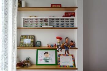 ベッド脇の棚にはミニチュアの車や人気アニメのフィギュア、そしてや子どもたちが描いた絵が飾られている。