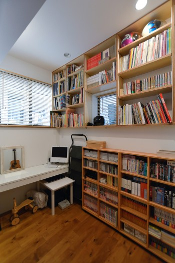 半地下の書斎。棚には神林さんが美術を手がけた番組のDVDが並ぶ。ここでセットのスケッチなどもするという。