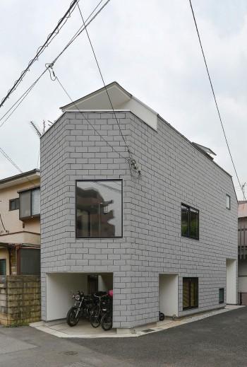 細長い形をした神林邸。通常は屋根材として使用されるアスファルトシングルを壁にも使って屋根・壁を一体化している。
