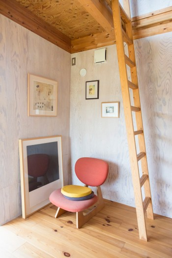 寝室のロフトに上がるはしご。友人の作品を飾ったスペースで寛ぐことも。