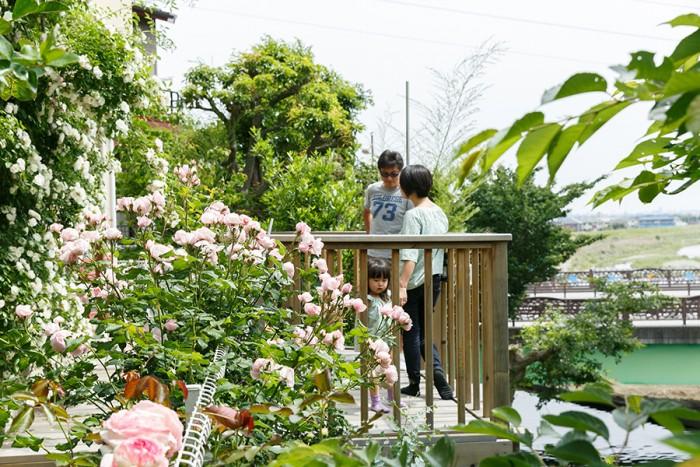バラが咲き乱れるデッキでくつろぐ夫妻とお子さん。