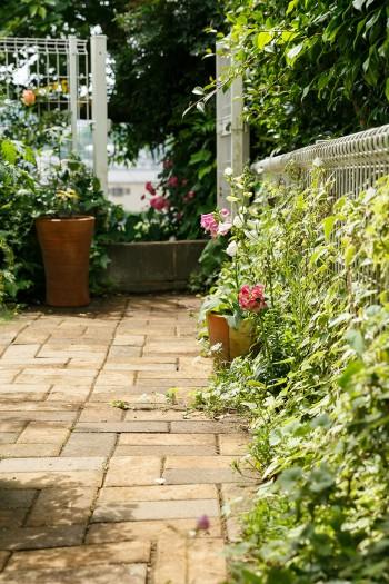 玄関から庭に向かうアプローチ。もともとは砂利敷きだったところを、啓介さんがレンガ敷きに。「できるだけ基礎を水平にならしてからレンガを敷いていくのですが、かなり苦労しました(笑)」。奥の扉の向こう側が、斜面の庭へと続いている。