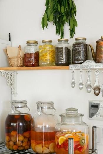 キッチンの奥には、手づくりの保存食を収納するコーナーが。お手製の梅酒や梅干し、果実酒などが並ぶ。上に吊るしているのは、庭の月桂樹の枝。