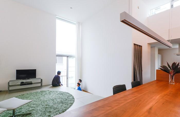 ダイニングから見る。リビングの床が窓前の床よりも55cm高く、座るのにちょうどいい高さになっている。中央の壁は、ホームシアターを大画面で楽しむために壁面が大きく取られている。