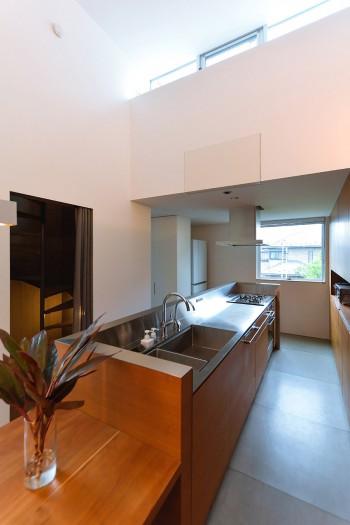 階段を上ってくるとキッチンの前に出る。キッチン奥の天井が低いため、吹き抜けの高さが体感的にさらに強調される。