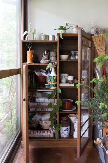 アンティークの棚に、園芸用の鉢や道具を収納。ブリキなどの金属ものも合わせ、変化をつけている。