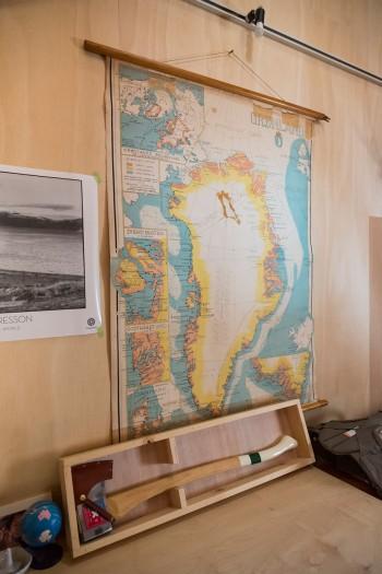 机の前には、いつかは行ってみたいというグリーンランドの古い地図。下は話題のアウトドアブランド『BEST MADE』の斧。