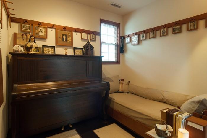 しょうこさんの部屋は聖テレーズが生きたヴィクトリア時代をイメージ。観音開きの扉を閉めると、静けさに包まれる。修道院を思わせる小さめのベッドは、昼間はソファーに。父親に買ってもらったピアノは黒から茶色に塗装し、今も大切にしている。