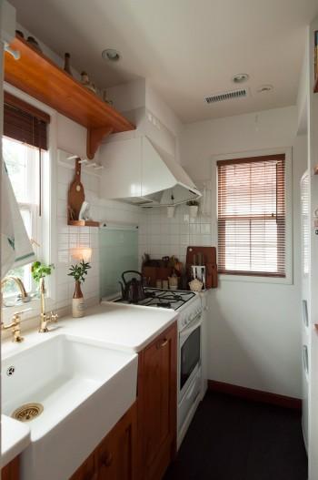 コンパクトで使いやすいキッチン。イギリスから取り寄せた陶器のベルファストシンクに、真鍮の蛇口、排水口が映える。
