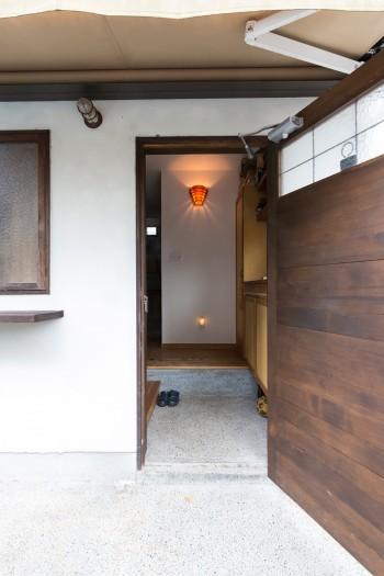 木をたくさん使うようリクエストした玄関。イメージに合わせて作り直したドアは、ガラスの部分に鉄の格子をアレンジ。
