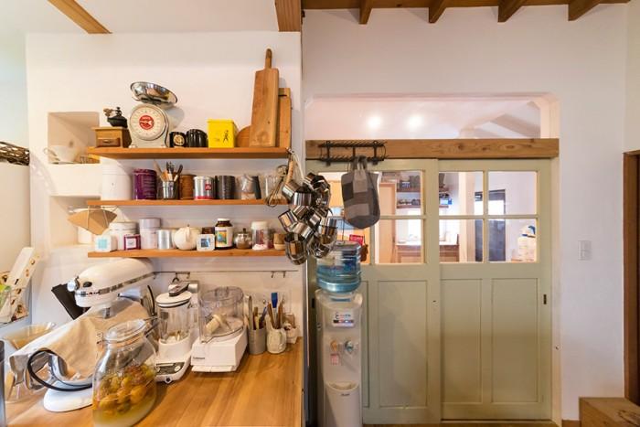学校の教室で使われていたと思われる薄い緑の引き戸も、ネットで購入。調理器具や材料もインテリアの一部に。