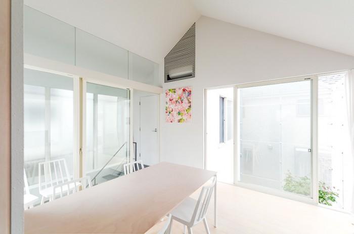 2階のリビングダイニング。庭を囲うエキスパンドメタルの壁を通して隣接する住宅の形がぼんやりと見える。テーブル天板は床と同じバーチ材を使用。浮遊感を出すために、エッジ部分に角度をつけて薄く見せている。椅子は藤森泰司氏デザインのもの。