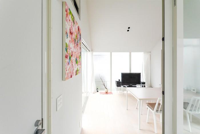 階段からリビングダイニングを見る。左は寝室。壁の絵は内海 聖史(さとし)さんの作品。この場所のために描かれた5作品から選ばれた2作品のうちのひとつ。外部環境を抽象化して取り込むという点ではこの住宅ともテーマが通じる。