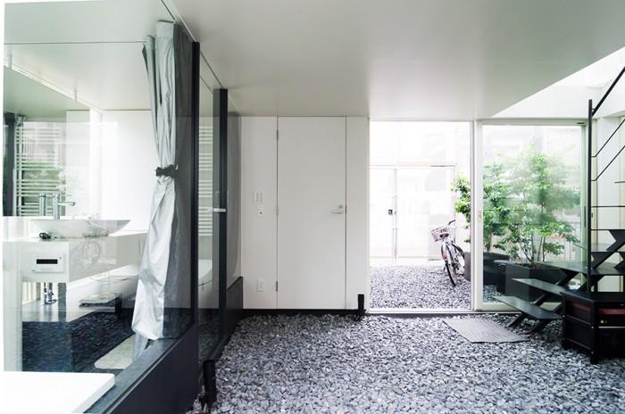 砂利空間からエントランス側を見る。左が浴室。砂利は大きさとグレーの色合いを指定して取り寄せたサンプルの中から選んだ。外の風景を映しこむように、この天井のみツヤのある仕上げにしている。
