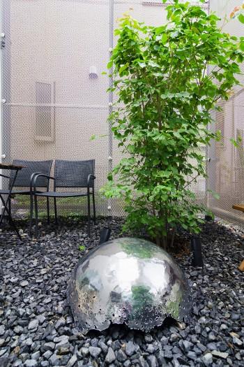 裏の庭に置かれた鍛金家の金森三恵子さんの作品。昼は周囲の風景を映しこみ、夜は照明となり砂利をなめるように光を放つ。