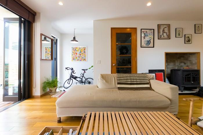 自転車が置いてある場所が玄関。正面のドアはアメリカ製のヴィンテージ。ドアの大きさに合わせて建具の枠を造作している。手前のテーブルはキャンプでも使える『INOUT』のもの。
