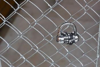 アルファベットのダイアル式の鍵を、扉のワイヤーに通してロックしている。