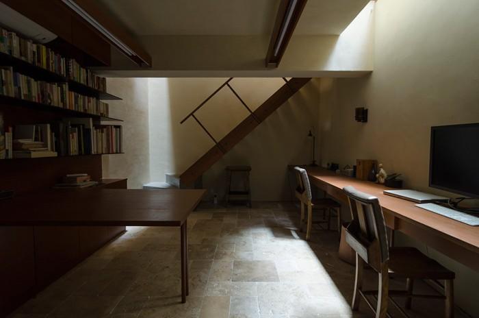 外光のみの状態の地下1階。光と陰のコントラストが美しい。奥の光はトップライトから落ちてきたもの。右の机で作業をするときは中庭の脇に設けられた明り取りから落ちてくる光のみで十分だ。