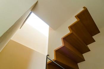 階段脇のヴォイドがトップライトの光を地階にまで導く。