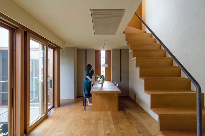 2階リビングからダイニングを見る。ダイニングから左に折れると右側にキッチンがある。正面のスリット状の窓の中心は、この家へと突き当たる道の中心と揃えているという。
