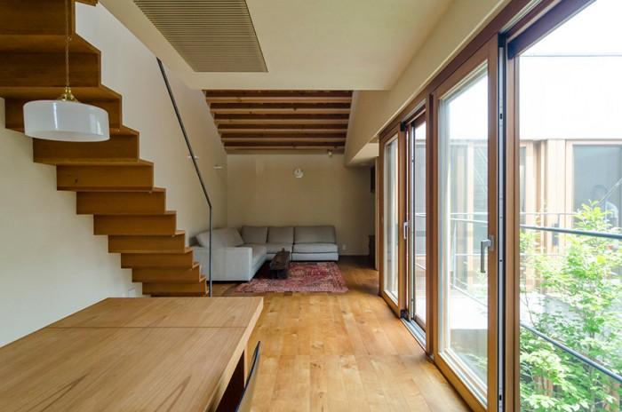 左の屋上へと続く階段は厚さ30mmの木板の踏み面と蹴上げだけでつくられた軽やかなつくり。左のダイニングテーブルは浅利さんのオリジナルデザイン。照明なども含め家具はほとんどこの家のためにデザインされたものという。