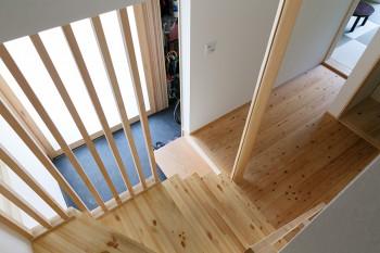 1階と2階をつなぐ階段から玄関を見る。玄関は引き戸、三和土はシックな墨色。