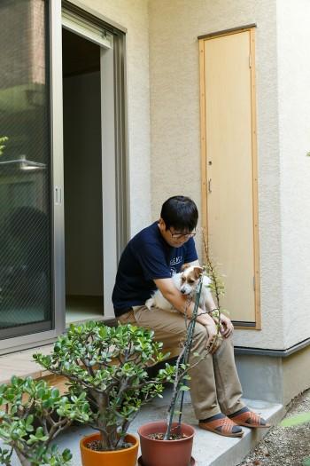 愛犬のポカラを連れて縁側でくつろぐ吉田さん。奥の扉には庭仕事の道具がしまえるようになっている。