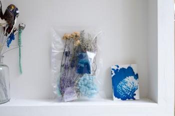 映像作家・島田大介氏の作品の一部を切り取った青写真とドライフラワーのセット。右側は島田氏の青写真をブックカバーにしたもの。