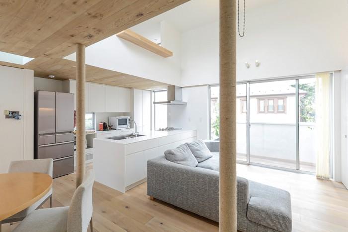 2 階ダイニング側からリビングとキッチンを見る。手前の柱は鉄柱に麻を手で巻いている。木を使用した床・天井とマッチして違和 感を感じさせない。キッチンは料理好きの夫婦の作業に子どもたちも参加できるようオープンなつくりにしている。