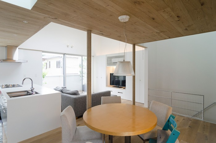 リビングの天井高3.9 mに対して手前のダイニングスペースは2.2 m。開放感のあるリビングに対して親密感のある空間になって いる。